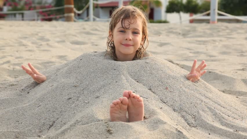 little girl with wet hair smiles siting filled up with sand on neck on beach