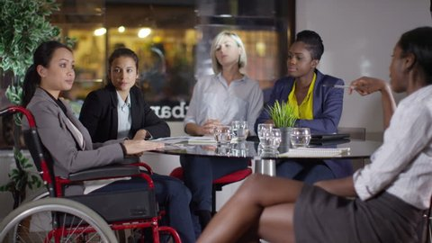 4k Confident female business group including woman in a wheelchair discuss ideas in office meeting. Shot on RED Epic.