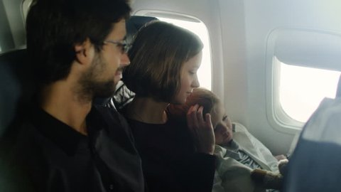 Romantic moment with a family with child on board of a plane next to a window. Shot on RED Cinema Camera in 4K (UHD).