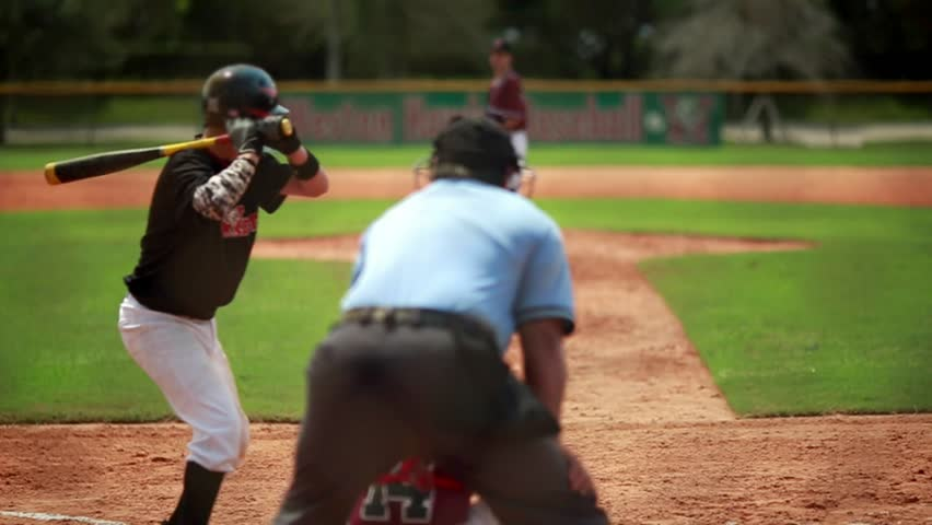 Really cool slow motion of a baseball player batting during a game and running towards first base.  All of the people including pitcher and catcher are unrecognizable.