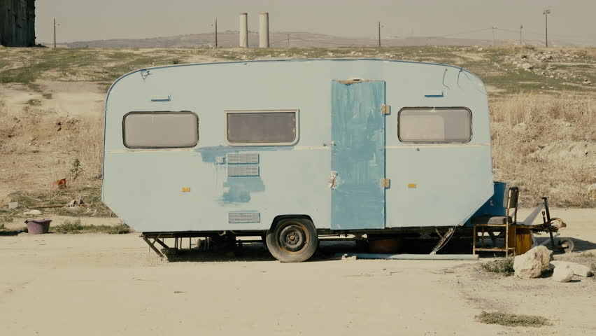 Rickety Old Vintage Abandoned Caravan Trailer In A Deserted Camp AreaAn Rusty Near Pier Close To An Industrial