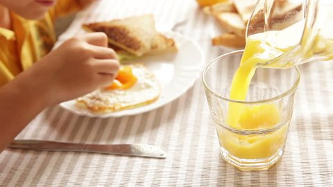 Mother pouring orange juice his little son during morning fried eggs breakfast