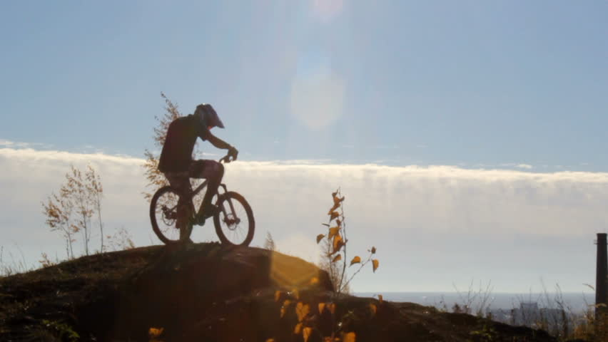Rider on a bike in front of a cloudy sky