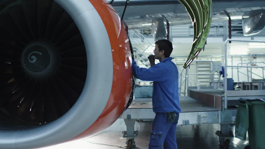 Aircraft Maintenance Mechanic With A Flash Light Inspects Plane ...