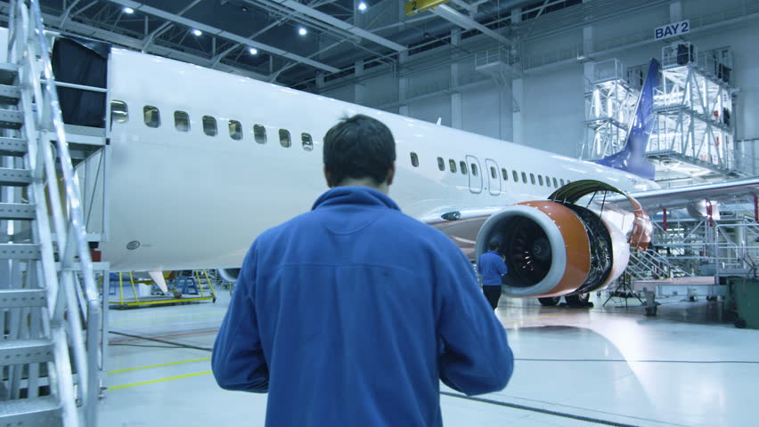 Aircraft maintenance mechanic in blue uniform is walking to greet his colleague who is checking the plane turbine blades in a hangar. Shot on RED Cinema Camera in 4K (UHD).