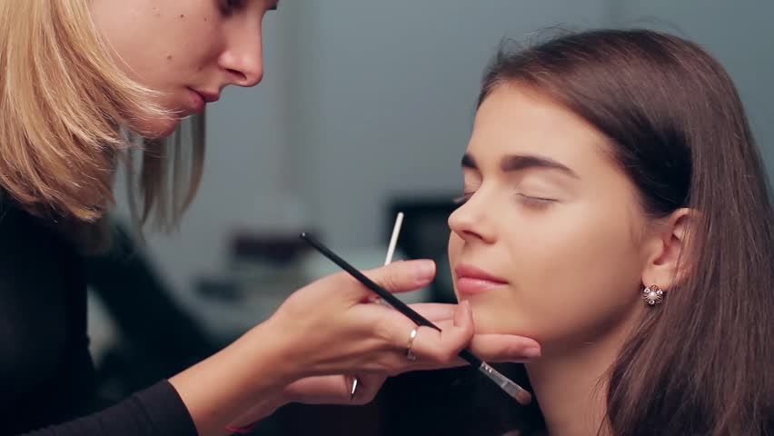 Specialist doing makeup for model. Gentle make-up for the young girl. Showing of models. Backstage of  fashion industry.