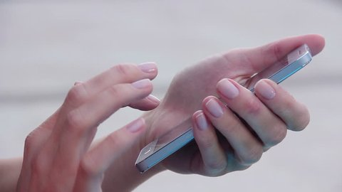Closeup shot of female hands holding smartphone, typing text on touch screen. Woman answering friend message in social network application, searching for information. Worker spending break time online