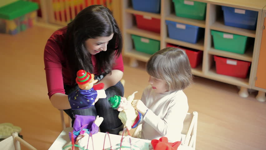School: girl and teacher playing with marionette in kindergarten. Sequence #1223647