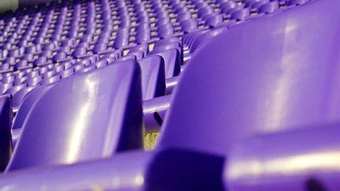 Rows of violet plastic seats on stadium tribune, dolly