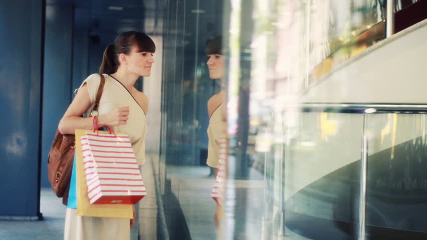 Attractive woman with shopping bags looking at shop window