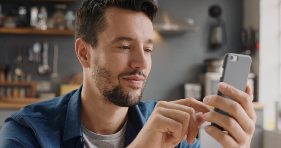 Attractive man at home using smartphone in kitchen sending message on social media smiling enjoying modern lifestyle wearing blue shirt | Shutterstock HD Video #12266195
