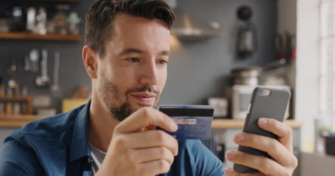 Man shopping online with credit card using smartphone at home lifestyle excited and happy about purchase connected banking mobile app