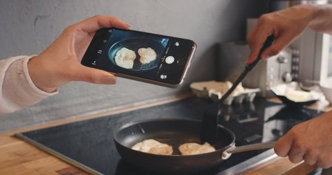 Happy couple Taking photo using smartphone of breakfast frying egg for social media lifestyle at home in kitchen