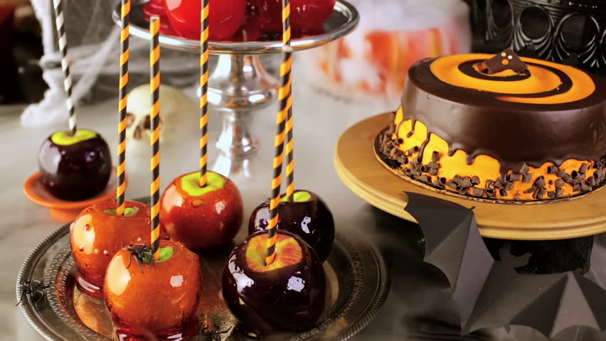 Table with colored candy apples and cake for Halloween party.