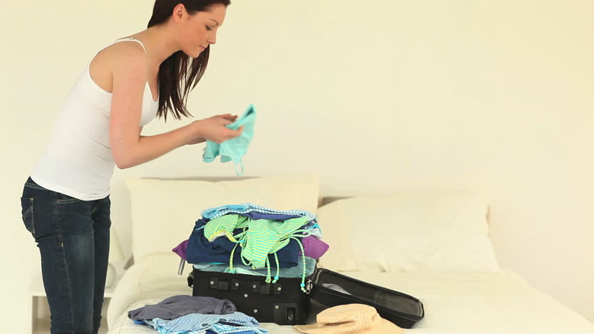 Good looking brunette woman packing up her suitcase in her bedroom