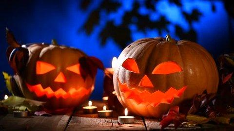 Halloween pumpkin head jack lantern with burning candles over black background. Halloween holidays art design, celebration. Stock video footage HD 1080p