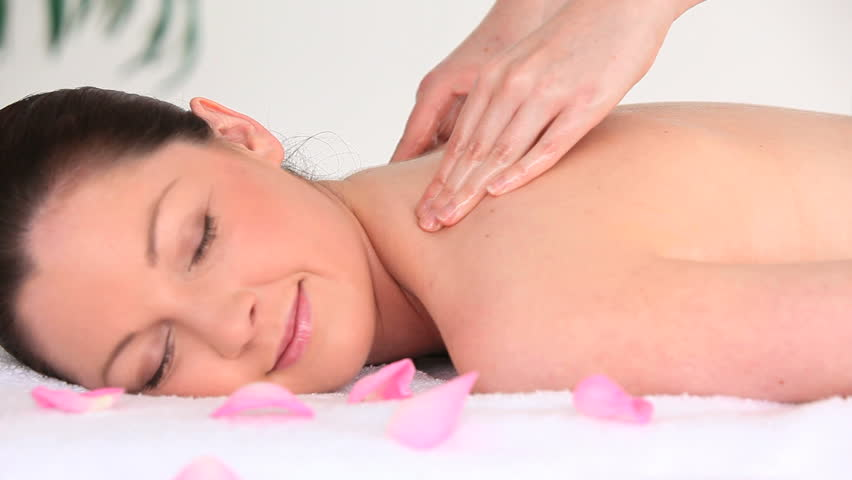 Portrait of a good looking dark-haired woman receiving a massage while lying on a towel in a spa center