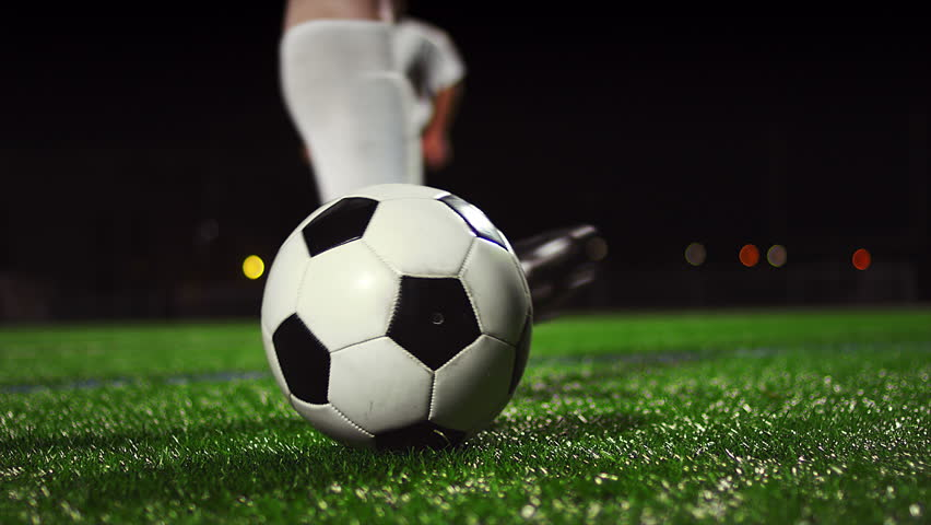 Close up of a soccer ball being kicked in slow motion at night #12304766