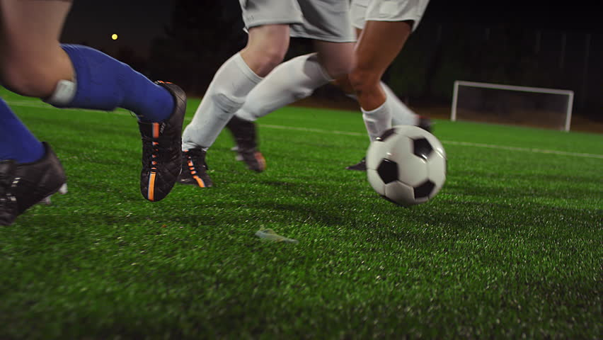 A female soccer player dribbles down the field at night while her opponents slide tackle and defend