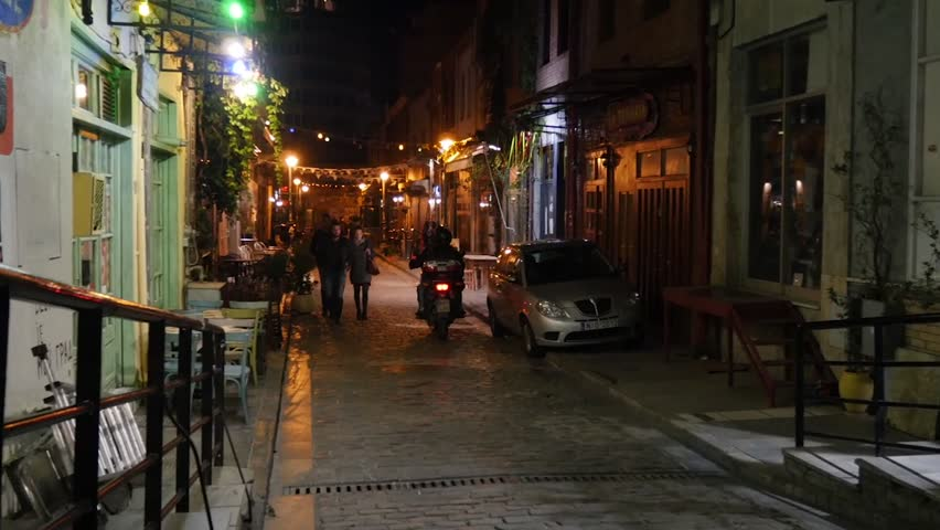 THESSALONIKI, GREECE - CIRCA 2015: Night life on a street in Thessaloniki, Greece with motorcycle passing and couple walking | Shutterstock HD Video #12308006
