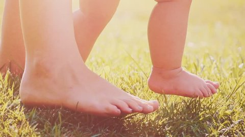 Little baby learns to walk. Close up on feet. Slow Motion 240 fps. Mother is teaching her child to do the first steps on a green grass in summer. Toddler is learning to walk outdoors on a green lawn.