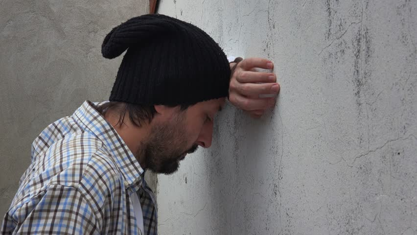 Troubled adult caucasian male banging his head against the wall, man with problems alone on the street.