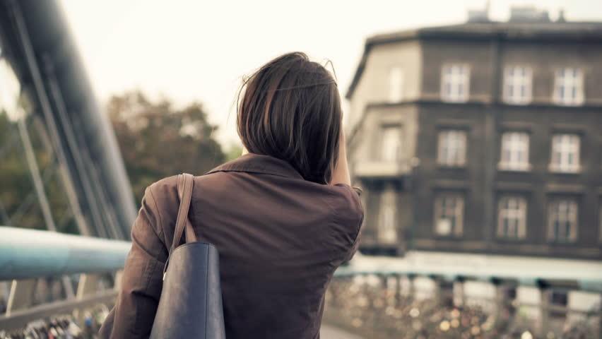 Woman walking across the bridge in the city