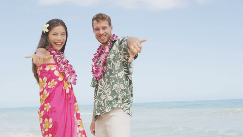 Asian woman and Caucasian man wearing flower lei garland and Aloha clothing  showing Shaka hand sign on travel.