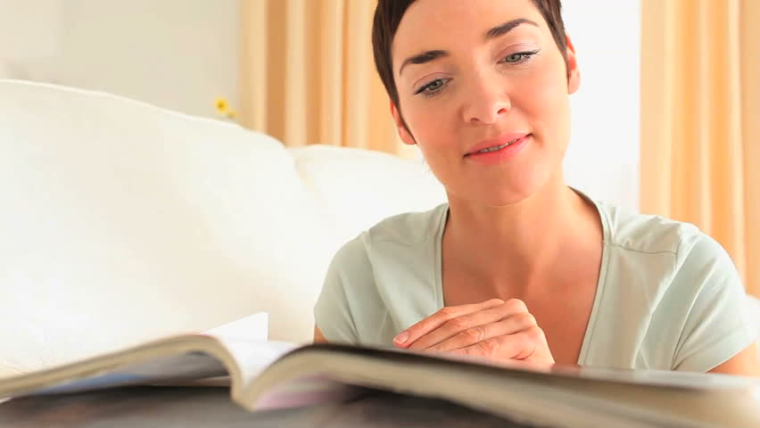 Brunette woman reading a magazine lying on a sofa
