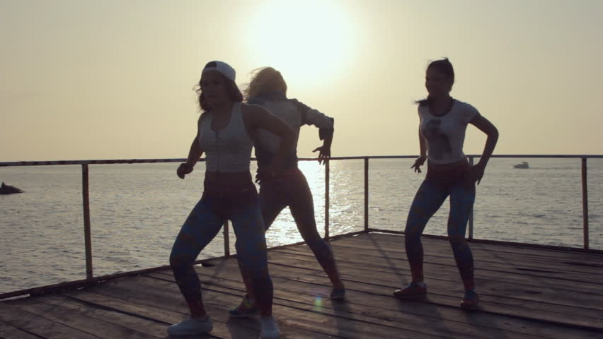 Training in dancing of three girls in same clothes on pier near the sea at sunset