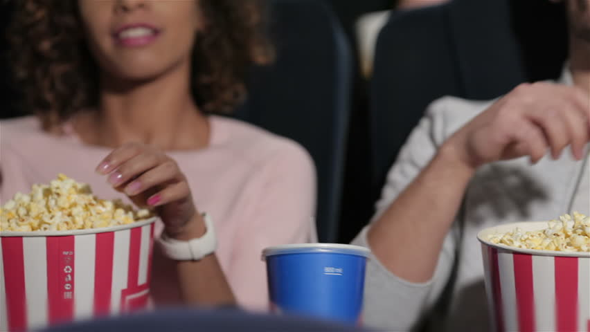 Couple in cinema theater watching a movie, they eating popcorn. Cinema, entertainment and people concept - happy friends watching movie in theater. Couple and other people eating popcorn and drinking | Shutterstock HD Video #12386711