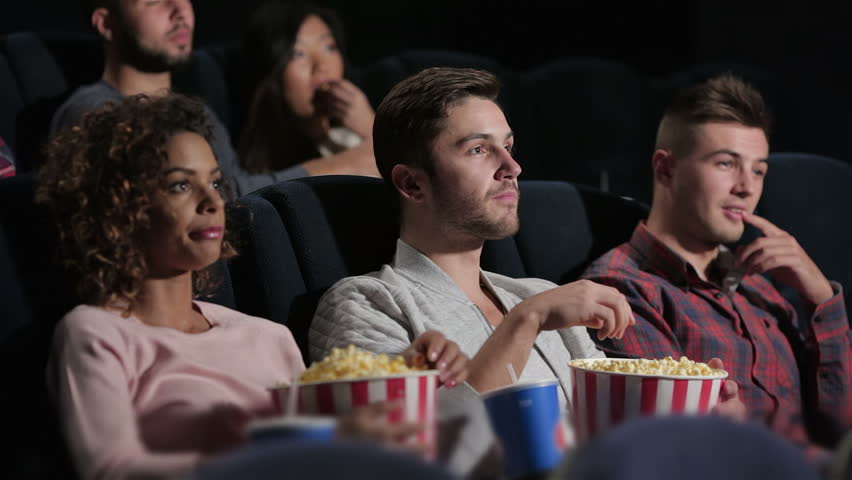 couple in cinema theater watching a movie they eating
