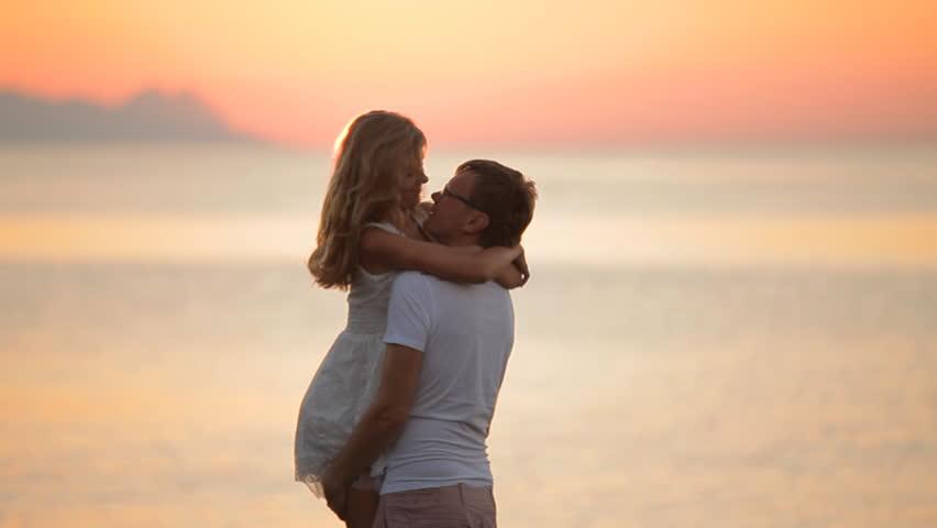 beautiful coupl posing at sunriset,walk along the sea,