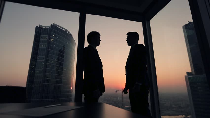 Two businessmen partners handshake in office. Silhouettes at sunset outside the window. | Shutterstock HD Video #12411758
