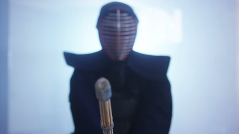 4K Portrait of a Japanese kendo fighter lowering his shinai towards the camera. Shot on RED Epic.