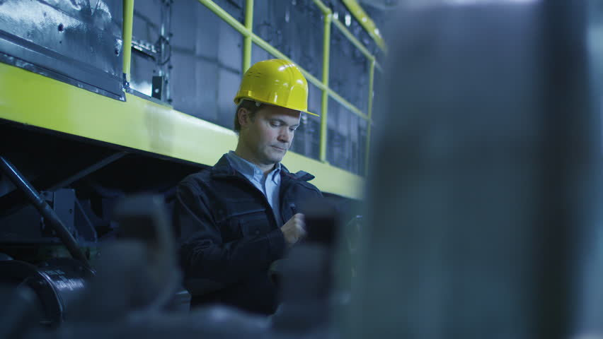 Technician in Hard Hat Using Mobile Phone in Industrial Environment. Shot on RED Cinema Camera in 4K (UHD).