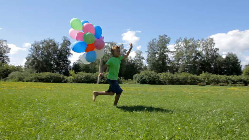 Happy boy running with many colorful balloons on green grass | Shutterstock HD Video #12427316