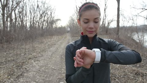 Runner using smartwatch fitness tracker and heart rate monitor watch jogging on trail in forest. Female athlete checking her cardio training data during workout outside in running park.