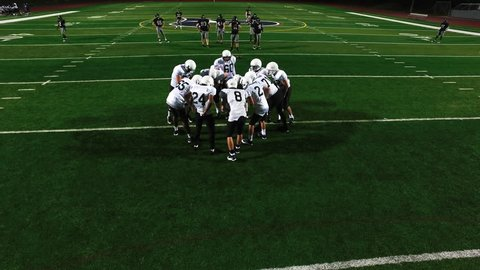 A football team in a huddle before a game, view from above