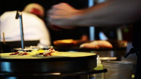 Restaurant chef cooks quesadilla.