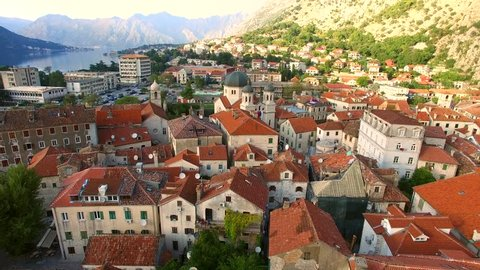 Flying above the old town of Kotor in Montenegro in the Bay of Kotor. Shooting from height, aerial view, aerial photography. Slow flight over the city. Autumn in Montenegro, warm November. Roof city