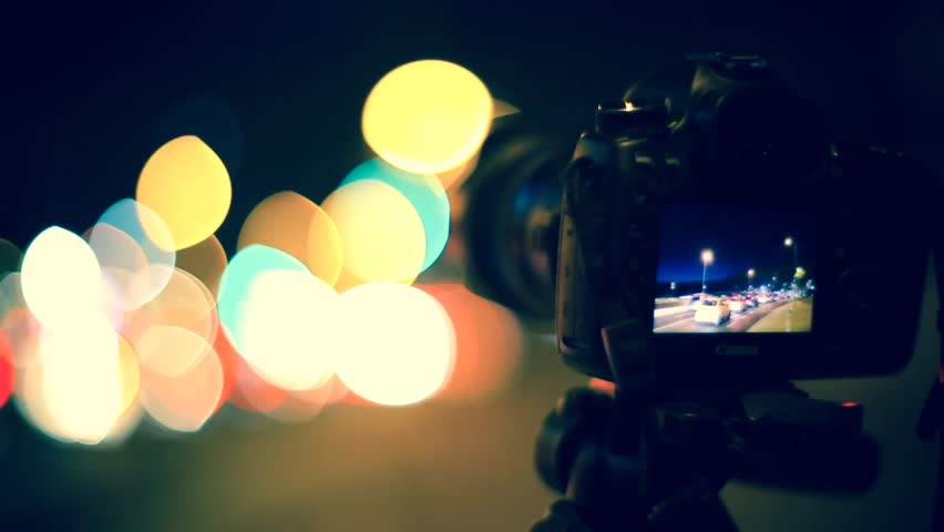 Cinemagraph Loop - Camera in foreground with blurred street lights in the background- motion photo