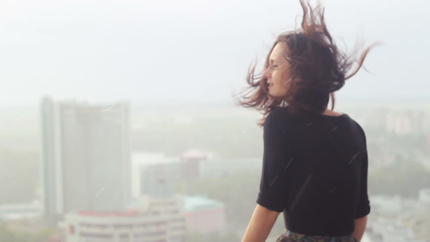 Young girl enjoys rain and sad at the roof. Wind blowing hair.
