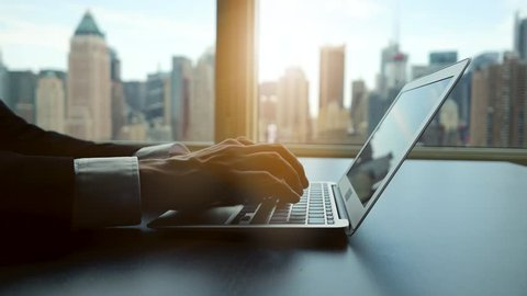 laptop desk view in modern business office. city skyline background.