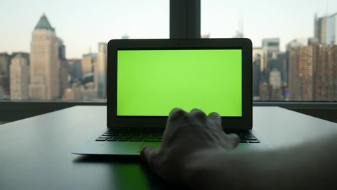 laptop desk view in modern business office. city skyline background. computer screen  isolated with green screen