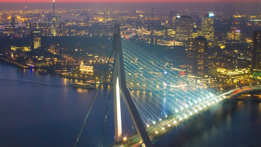 Long exposure static timelapse of the famous erasmus bridge in with the urban skyline of one of europe's biggest harbours in Rotterdam, the Netherlands
