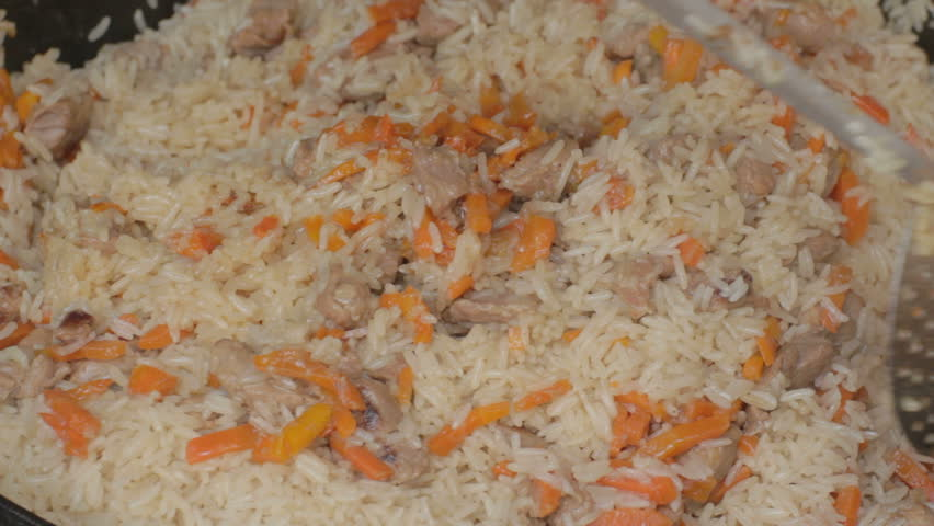 Thoroughly mixing with slotted spoon ready flavorful pilau