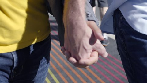 Closeup Of Gay Couple Holding Hands, Walking Toward Camera, Across Rainbow Colored Crosswalk In San Francisco