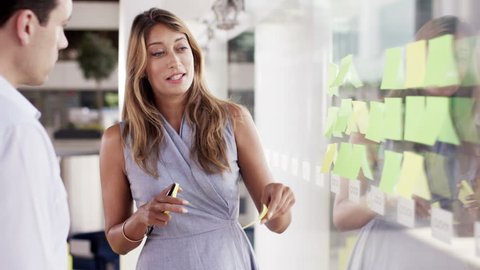 4K Attractive business man and woman brainstorming for ideas with sticky notes in modern office. Shot on RED Epic.