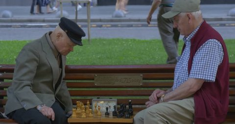 LVIV/UKRAINE - JUL 14 2015: Two Men Are Sitting in Front of Each Other on The Bench, Senior Aged Men in Caps, Playing Chess, Mid Shot, Turn Chess Clocks, Chess Board,the players take turns moving one